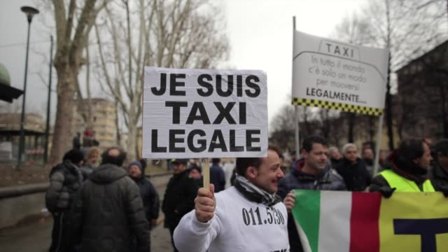 Italian taxi drivers demonstrate in Turin against minicabs and the taxi app offered by Uber UberPOP which they consider being unfair competition