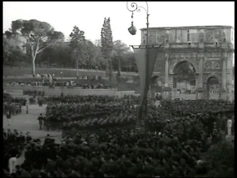 vídeos de stock e filmes b-roll de italian troops gathered marching in street w/ arch bg italian troops gathered w/ coliseum bg - 1935