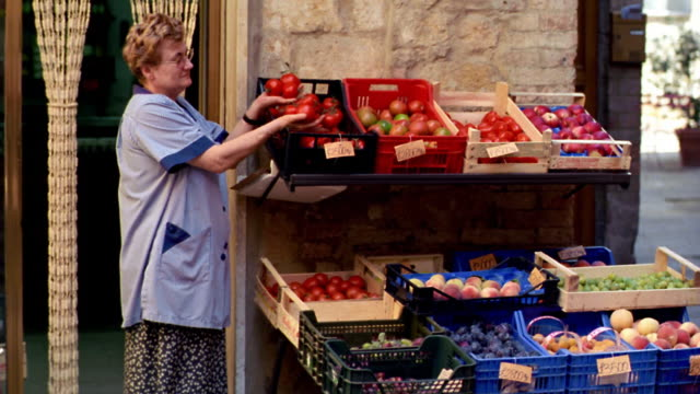 italian woman putting tomaotes in bin at vegetable stand / pienza, italy - italian culture stock-videos und b-roll-filmmaterial