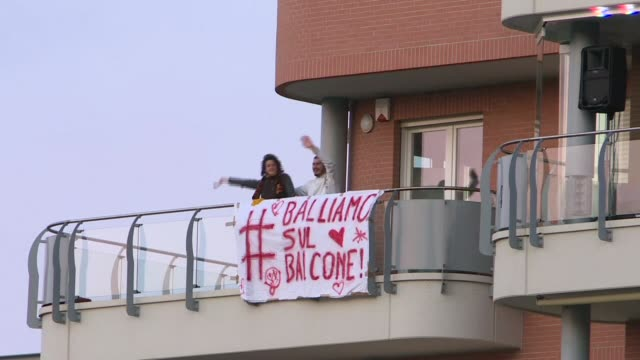 italians dance at their windows and on their balconies as they carry on with government imposed selfisolation amid the coronavirus pandemic - balcone video stock e b–roll