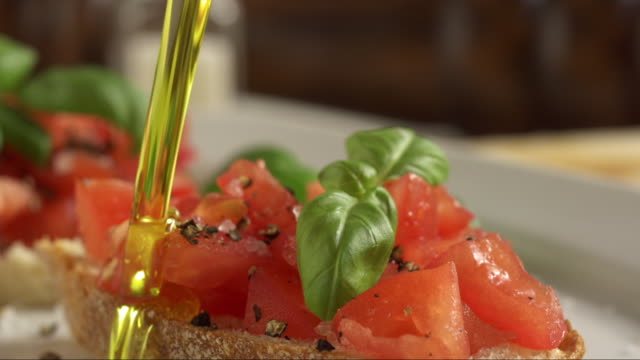 italien olive oil pouring on tomato basil bruschetta - olive oil stock videos & royalty-free footage
