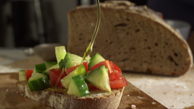 italien olive oil pouring on tomato cucumber bruschetta - peasant bread stock videos and b-roll footage