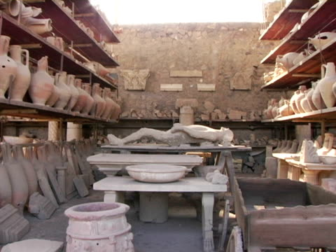 MS, Italy, Pompeii, Plaster cast of person  and rows of vases on display