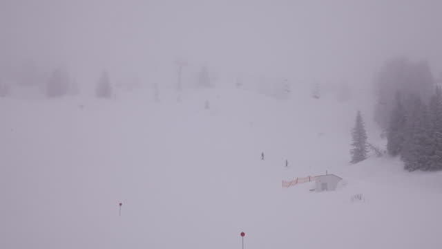 It´s a very foggy moment in the mountains. Some persons are skiing and thee ski lists are moving.