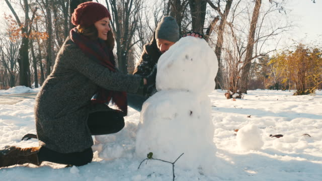 it`s always a joy to make a snowman. - making a snowman stock videos & royalty-free footage