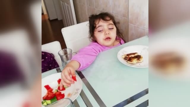 it's an ageold dilemma whether to eat or sleep a video taken by a turkish mother in istanbul shows her threeandhalfyear old daughter doing both at... - baby girls stock videos & royalty-free footage