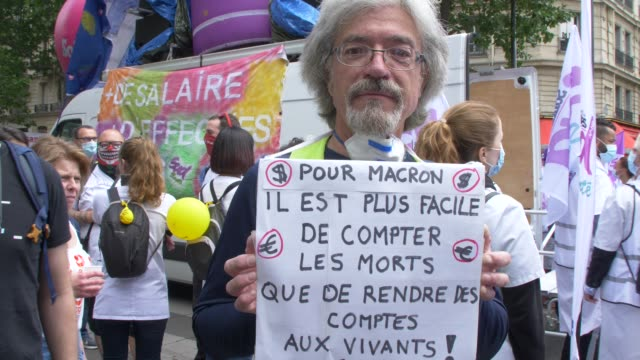 it's easier for macron to count the dead than to account for the living says the sign of a participant in the white coat demonstration paris 16 june... - participant stock videos & royalty-free footage