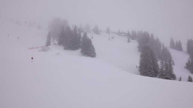 It´s foggy and it´s snowing on the snowy landscape in the mountains. People skiing and ski lift at the bottom.