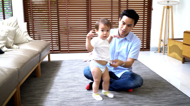 it's hard to dress the child while he want to play every time - genderblend stock videos & royalty-free footage