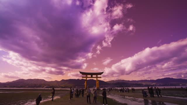 ws t/l itsukushima shrine's sacred torii gate at low tide in miyajima island / miyajima, hiroshima prefecture, japan - bassa marea video stock e b–roll