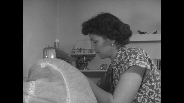 vídeos y material grabado en eventos de stock de iva sprout, wife of usaaf veteran dale sprout, works at sewing machine in room of their homestead house; she sews a dress / vs iva looks at the... - iva