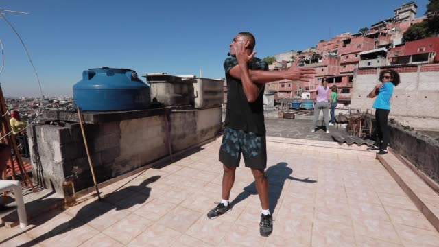 ivan pereira do nascimiento, 39 years old physical education student conducts training sessions from the roof of his house to residents of... - exercising stock videos & royalty-free footage