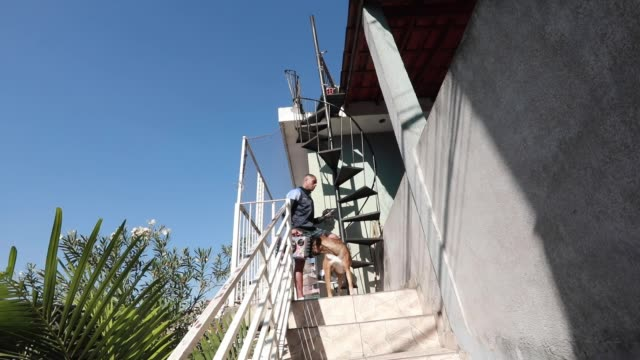 vídeos de stock, filmes e b-roll de ivan pereira do nascimiento a 39 year old physical education student heads up the stairs to conduct training sessions from the roof of his house to... - pet equipment