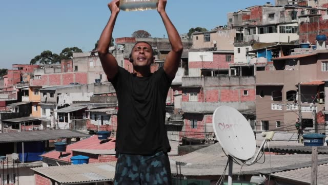 vídeos de stock, filmes e b-roll de ivan pereira do nascimiento a 39 year old physical education student conducts training sessions from the roof of his house to residents of... - pet equipment