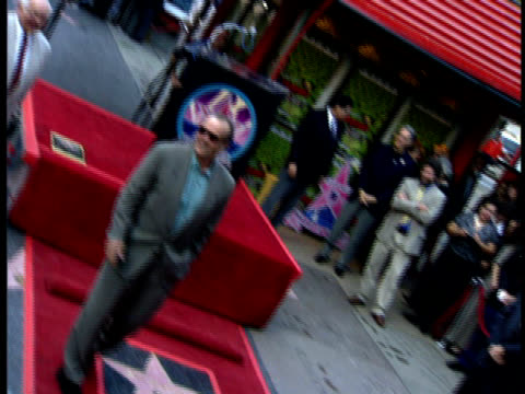 jack nicholson poses next to the star he has received on the walk of fame. - jack nicholson stock videos & royalty-free footage