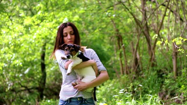 vídeos y material grabado en eventos de stock de jack russell terrier de cachorro en un tierno abrazo de atractiva rubia mujer oscuridad - terrier