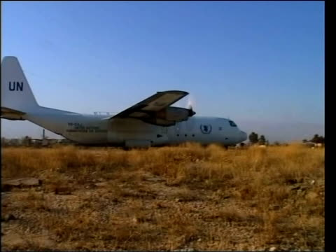 jack straw in iran / humanitarian response; afghanistan: bagram airbase: un c-130 transport plane taxiing at airbase mss volunteers unloading boxes... - bagram stock-videos und b-roll-filmmaterial