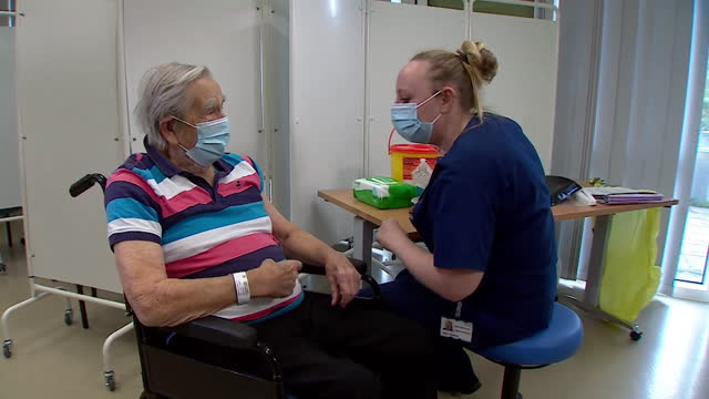 jack vokes, the first person to receive the covid-19 pfizer biontech vaccine at bristol southmead hospital, joking with nurse and talking about his... - excitement stock videos & royalty-free footage