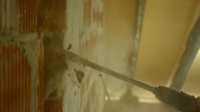 壁をコツコツ slo mo 削岩機 - レンガの壁点の映像素材/bロール