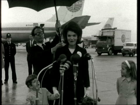 jackie kennedy and family depart from london; england: london: lap : jackie kennedy walks as man holds umbrella over her jackie with children and... - jackie kennedy stock videos & royalty-free footage