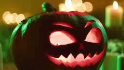 Jack-o-lantern and blowing burning candles close-up. Carved pumpkin with fire flame inside standing on wooden table. Halloween symbols, scary face, traditional autumn holiday decorations