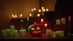Jack-o-lantern and burning candles close-up. Carved pumpkin with fire flame inside standing on wooden table. Halloween symbols, scary face, traditional autumn holiday decorations