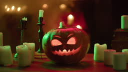 Jack-o-lantern and extinguished candles close-up. Carved pumpkin with fire flame inside standing on wooden table. Halloween symbols, scary face, traditional autumn holiday decorations
