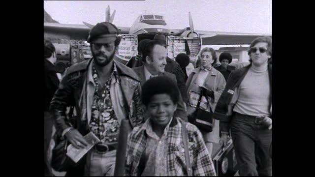 Jackson 5 and entourage in 1973 including Michael Jackson and Joe Jackson walking across tarmac at Wellington Airport