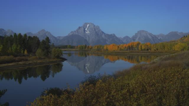 jackson lake reflects a portion of the grand teton range. - grand teton stock-videos und b-roll-filmmaterial