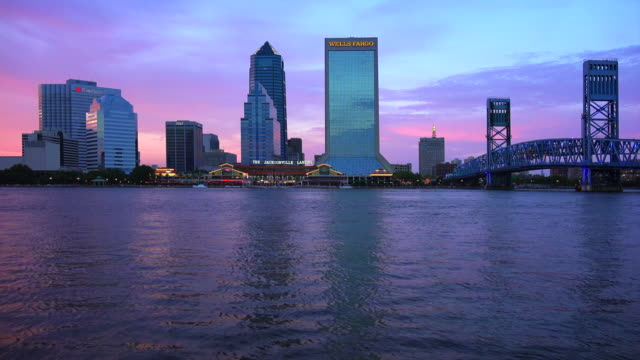 jacksonville, florida city skyline over the st. john's river at sunset - jacksonville florida video stock e b–roll