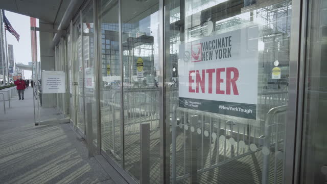 "jacob javits center entrance / exit door with ""vaccinate new york - #newyorktough"" sign. filmed during the coronavirus pandemic . video by thompics -... - exit sign stock videos & royalty-free footage"