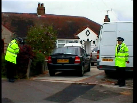 andrew wragg gives evidence; file / tx 27.7.04 worthing: police outside wragg family home wheelchair propped against wall of house - worthing点の映像素材/bロール