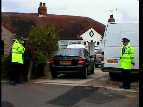 father's murder trial continues; date unknown worthing: police officers outside wragg family home police vehicle among other cars outside house... - worthing点の映像素材/bロール