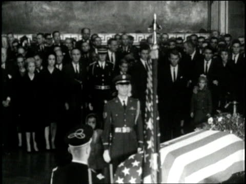 jacqueline and caroline kneel beside u.s. president john f. kennedy's flag-draped coffin as it lies in state in rotunda of capitol building. - coffin stock videos & royalty-free footage