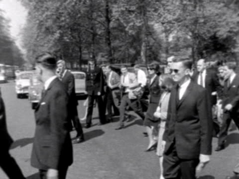 stockvideo's en b-roll-footage met jacqueline kennedy and her children leave green park and walk towards buckingham palace surrounded by bodyguards and the press 1965 - jacqueline kennedy