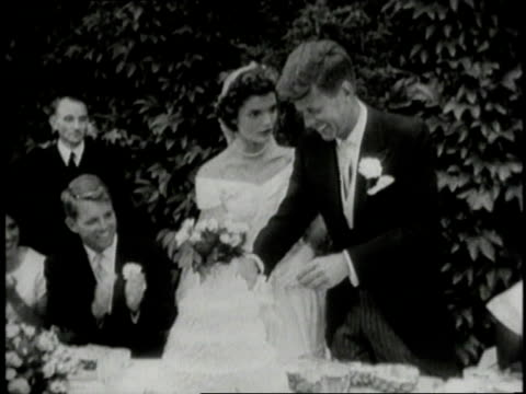 stockvideo's en b-roll-footage met jacqueline kennedy onassis and john f kennedy cutting the cake at their wedding reception / newport rhode island united states - jacqueline kennedy