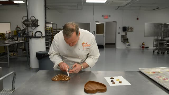 jacques torres a chocolate chef works with a chocolate mixer filled with chocolate dyed red with food coloring at his jacques torres chocolate... - food coloring stock videos and b-roll footage