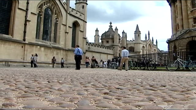 report from oxford england oxfordshire oxford ext low angle shot of people to and fro along cobbled street cyclists along university spires railings... - guglia video stock e b–roll
