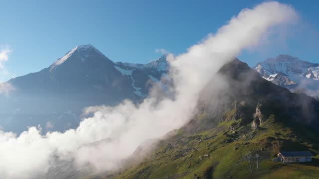 vídeos de stock e filmes b-roll de jagged mountain peaks rise above clouds on sunny, blue-skied day - televisão de ultra alta definição