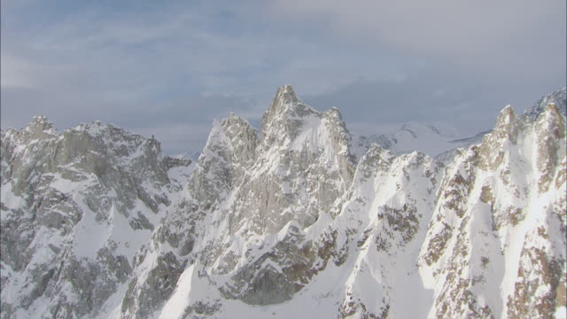 aerial jagged peaks and cliffs of snow-covered mountain range and expansive valley / alaska - アラスカ点の映像素材/bロール