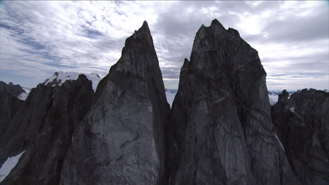 jagged peaks tower over a snowy valley in alaska. - アラスカ点の映像素材/bロール