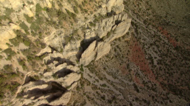 jagged rock covers the winding edge of land formations in the grand canyon. - felswand stock-videos und b-roll-filmmaterial