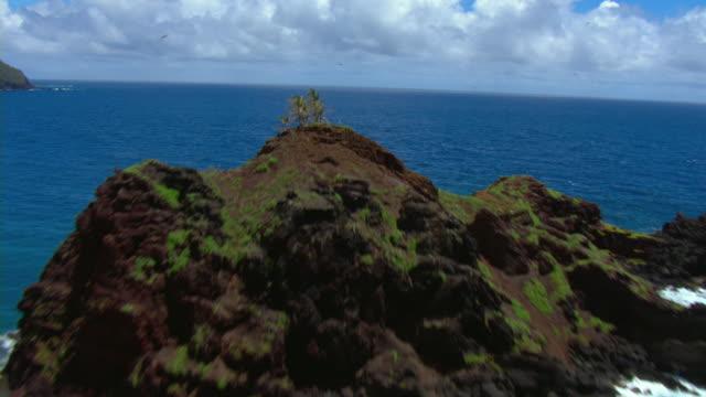 vídeos y material grabado en eventos de stock de a jagged rock formation juts out of the pacific ocean off the coast of maui. - tosco
