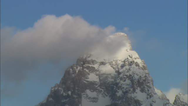 ms jagged, rugged snow covered peak of teton mountains against blue sky with white cloud passing in foreground / grand teton national park, wyoming, usa - teton range stock videos & royalty-free footage