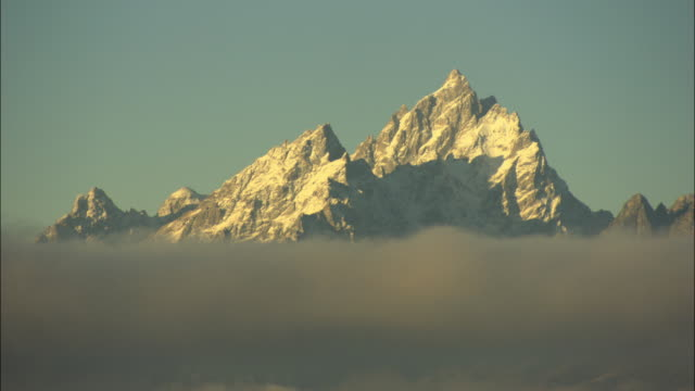 zo ws jagged, snow covered grand teton mountain peak rising of low cloud layer and grassy plain covered in fog / grand teton national park, wyoming, usa - alm stock-videos und b-roll-filmmaterial