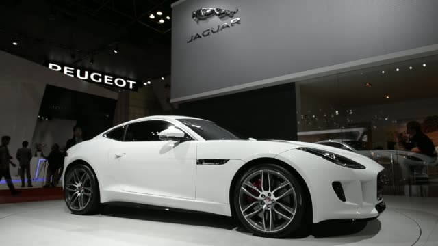 a jaguar ftype r coupe vehicle stands on display at the 43rd tokyo motor show 2013 in tokyo japan on thursday nov 21 jaguar xj portfolio car left and... - day 2 stock videos and b-roll footage