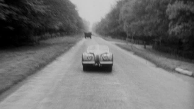 vidéos et rushes de 1952 b/w jaguar xk-120 driving on highway / united kingdom - 1952