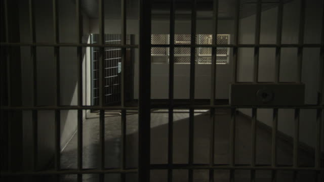 a jail cell looks out at a hallway. - prison bars stock videos and b-roll footage