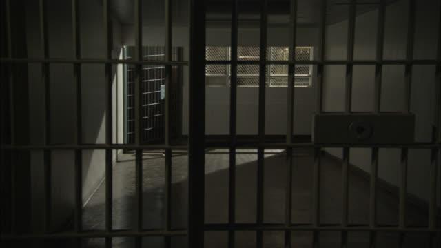vídeos de stock, filmes e b-roll de a jail cell looks out at a hallway. - grade de prisão