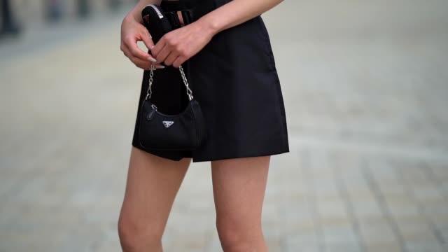 stockvideo's en b-roll-footage met jaime xie wears an alexander wang black cropped top, a prada short skirt, a prada belt, a prada bag, versace pointy boots, a prada tie, on september... - versace modelabel